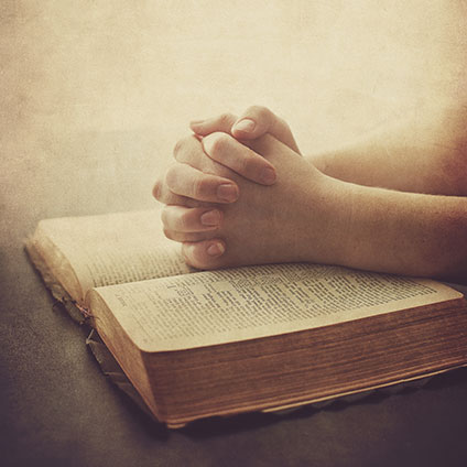two-hands-are-on-a-bible-in-prayer_rXnZ11MeA_424